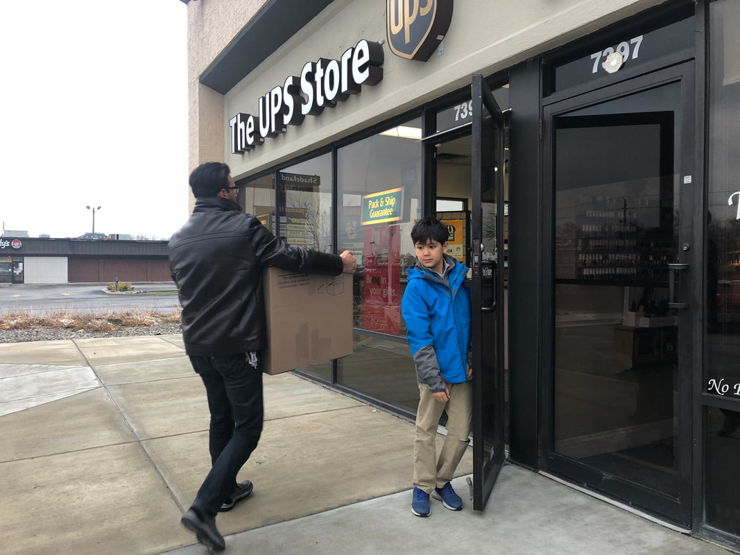 Yasseen and Mohamed delivering 2 boxes of shoes to the UPS Store to be shipped to Soles4Soles
